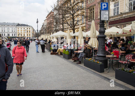Tourists eat and drink in main market Krakow - Stock Photo