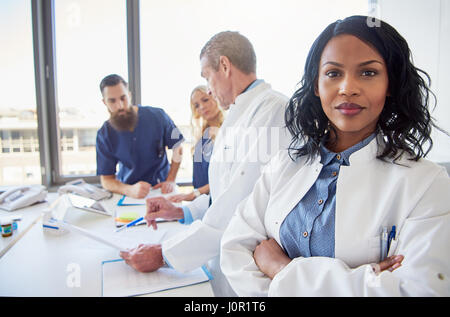 Black female doctor standing with arms crossed and looking at camera during the meeting in hospital. - Stock Photo