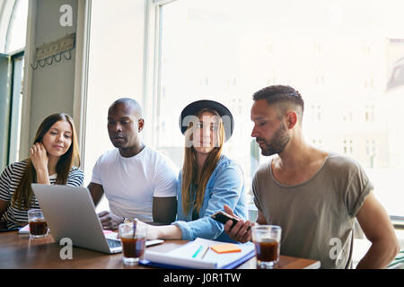 Group of four young co-workers sitting at table with laptop and having coffee while discussion in office. - Stock Photo