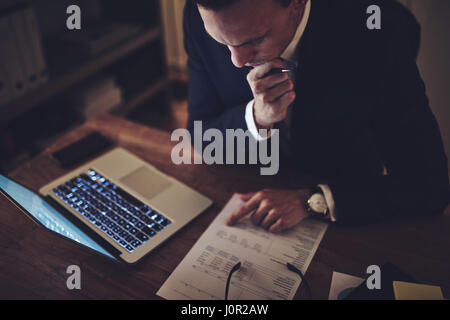 Thoughtful businessmansitting in the office and doing the paperwork at night. - Stock Photo