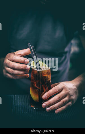 Barman is decorating rum based drink cocktail with lime - Stock Photo
