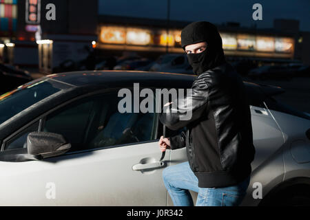 Male Car Thief Hands Trying To Open Door With Jemmy