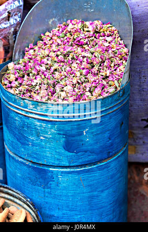 Rose petals on street stall in blue barrel - Stock Photo