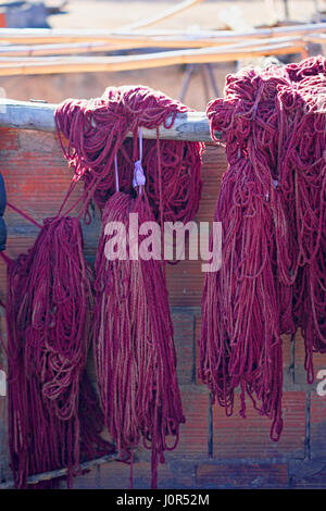 Bundles of dyed violet wool drying in the souks of Marrakesh - Stock Photo