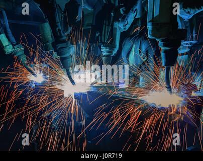 Industrial welding robots in production line - Stock Photo