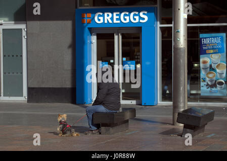 lonely hooded person with yorkie dog epitomising Greggs st Enoch Glasgow