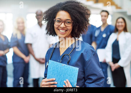 Smiling young black female doctor standing in front of medical team at hospital - Stock Photo