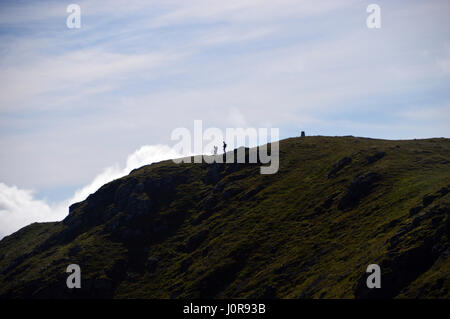 Silhouettes of a Pair of Walkers on the Summit of the Scottish Mountain Corbett Ben Ledi in the Trossachs Natianal - Stock Photo