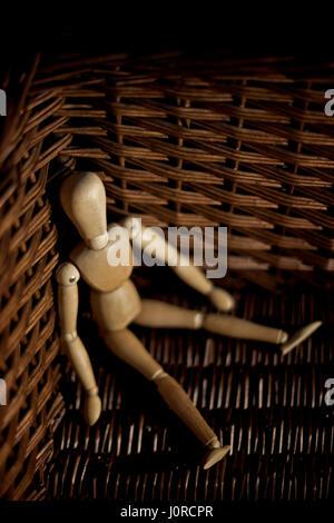 Wooden model mannequin in a wicker basket. - Stock Photo