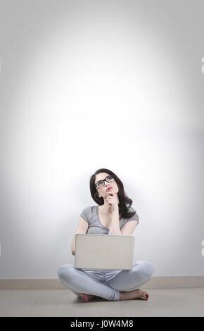 Woman with laptop thinking - Stock Photo