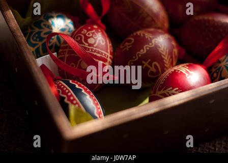 colorful handmade Easter eggs in wooden box - Stock Photo