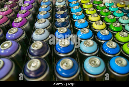 colorful cans of paint stand rows on a shelf - Stock Photo