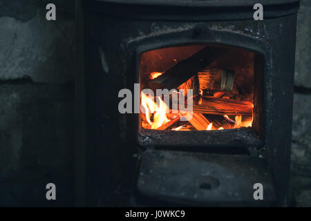 Fire burning in black iron stove. Closeup photo with selective focus - Stock Photo