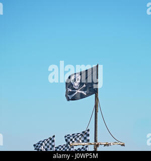 The skull and crossbones of the traditional pirate flag known as the Jolly Roger flying high against a blue sky - Stock Photo