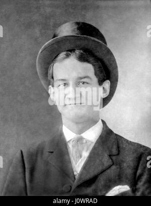 Vintage b&w portrait of a young man about eighteen-years old wearing a Victorian beaver top hat around 1915. - Stock Photo