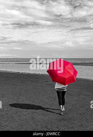 A woman walks on the beach with an open red umbrella. This photo is a color drop out with a conversion to grey scale - Stock Photo