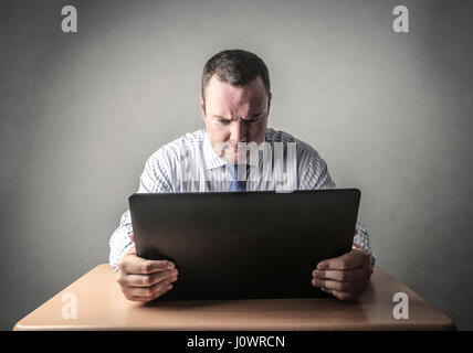 Businessman sitting in front of laptop - Stock Photo