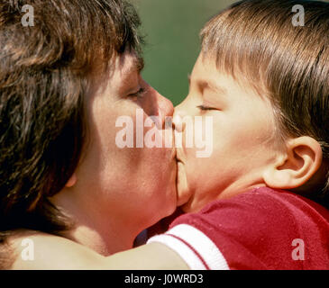 A cute three-year old boy plants a huge kiss on his mother in Plainfield, New Hampshire, United States. - Stock Photo