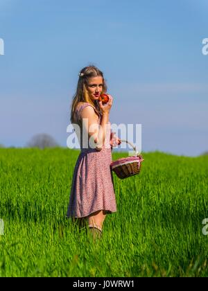 Country-girl with small basket in hand looking at camera eyes-contact through grass farm girl - Stock Photo