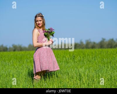 Country-girl with flowers in hands looking back side view farm girl isolated blur blurred background standing alpfabet - Stock Photo