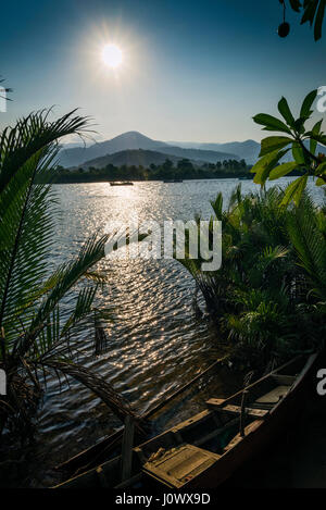 tropical exotic sunset riverside view in kampot cambodia asia with fishing boat - Stock Photo