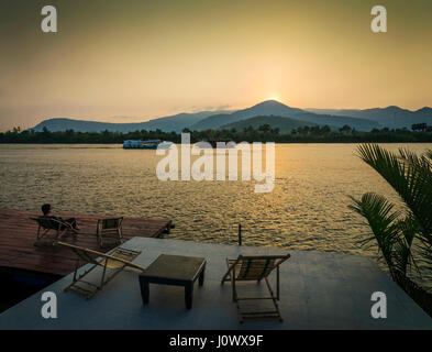 riverside sunset view in kampot cambodia asia with relaxing deck chairs and ferry boats - Stock Photo