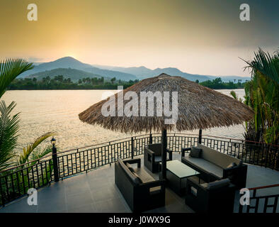 riverside sunset view in kampot cambodia asia with relaxing deck sofa chairs and table - Stock Photo