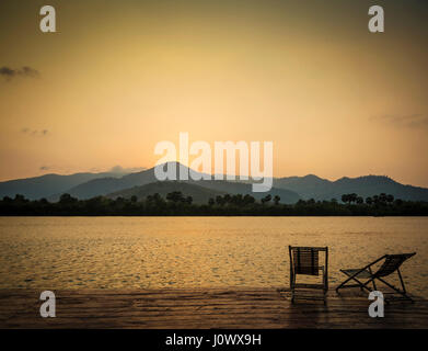 tropical exotic sunset riverside view in kampot cambodia asia with deck chairs - Stock Photo