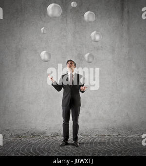 Businessman juggling with balls - Stock Photo