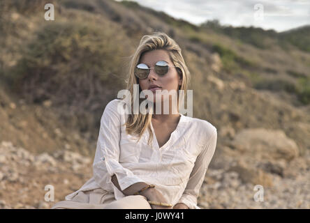 blond woman in sunglasses resting on beach - Stock Photo