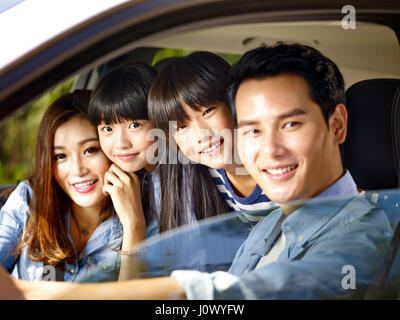 happy asian family with two children riding in a car - Stock Photo