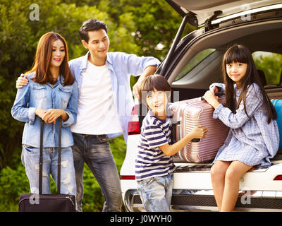 cute asian children helping unloading luggage from trunk while parents watching affectionately. - Stock Photo