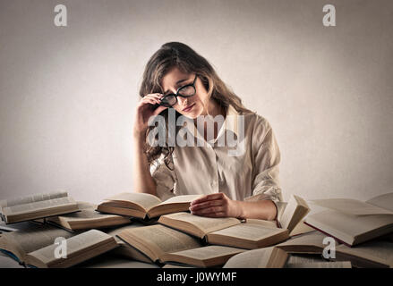 Woman studying from multiple books - Stock Photo