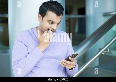 Closeup portrait, funny young man, shocked surprised, biting fingernails, by what he sees on his cell phone, isolated - Stock Photo
