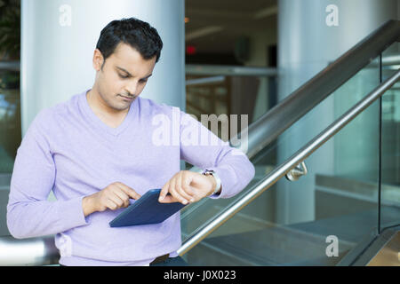 Closeup portrait, serious young man in purple sweater checking syncing blue smartpad with smart watch, isolated - Stock Photo