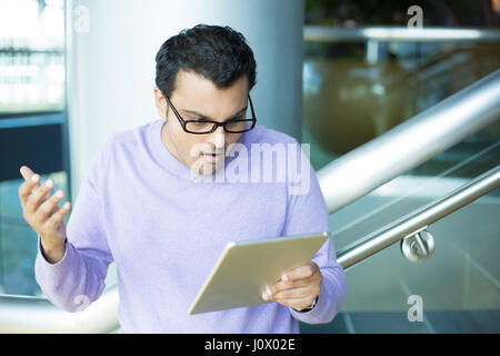 Closeup portrait, young angry man in black eyeglasses and purple sweater, astonished, wide open mouth, by what he - Stock Photo
