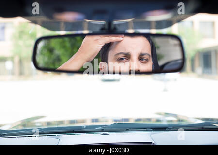 Closeup portrait, funny young man driver looking at rear view mirror looking at hair loss issues widow's peak or - Stock Photo