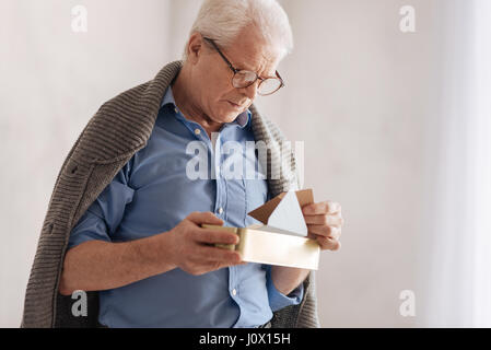 Nice elderly man being nostalgic about his past - Stock Photo