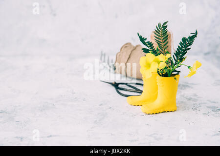 wellington boots with flowers and gardening tools - Stock Photo