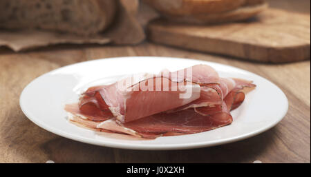 Italian speck ham on a plate on wood table - Stock Photo