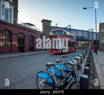 London new red Routemaster bus in Camden Town passing the Hawley Arms and a row of cycles for hire - Stock Photo