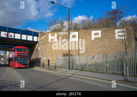 New London red Routemaster bus on York Way near King's Cross passing graffiti by Hope - Stock Photo
