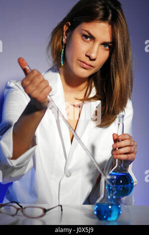 Laboratory female worker selecting flasks with analyses while holding one containing blue fluid inside - Stock Photo