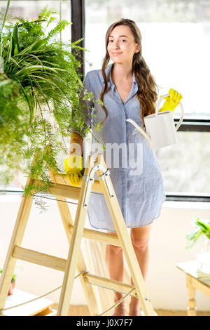 Young gardener in the orangery with green plants - Stock Photo