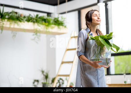 Woman with plant at home - Stock Photo