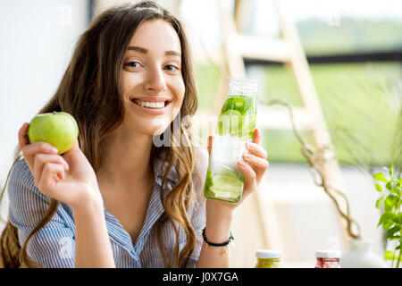 Woman with green healthy food and drinks at home - Stock Photo