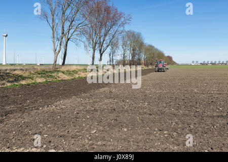 Red tractor plough at bare Dutch field in early springtime - Stock Photo