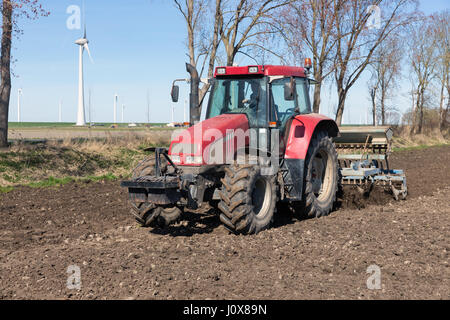ESPEL, THE NETHERLANDS - MARCH 25, 2017: Red tractor plough at bare Dutch field in early springtime - Stock Photo
