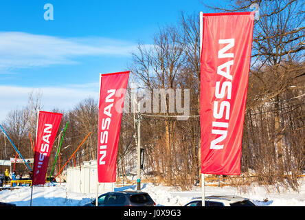 SAMARA, RUSSIA - FEBRUARY 14, 2016: Dealership flags Nissan over blue sky in sunny day. Nissan is a Japanese multinational - Stock Photo