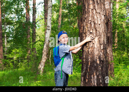 Child (boy, hands) hugging pine (big tree), playing and having fun outdoor in summer forest (park). Environmental - Stock Photo